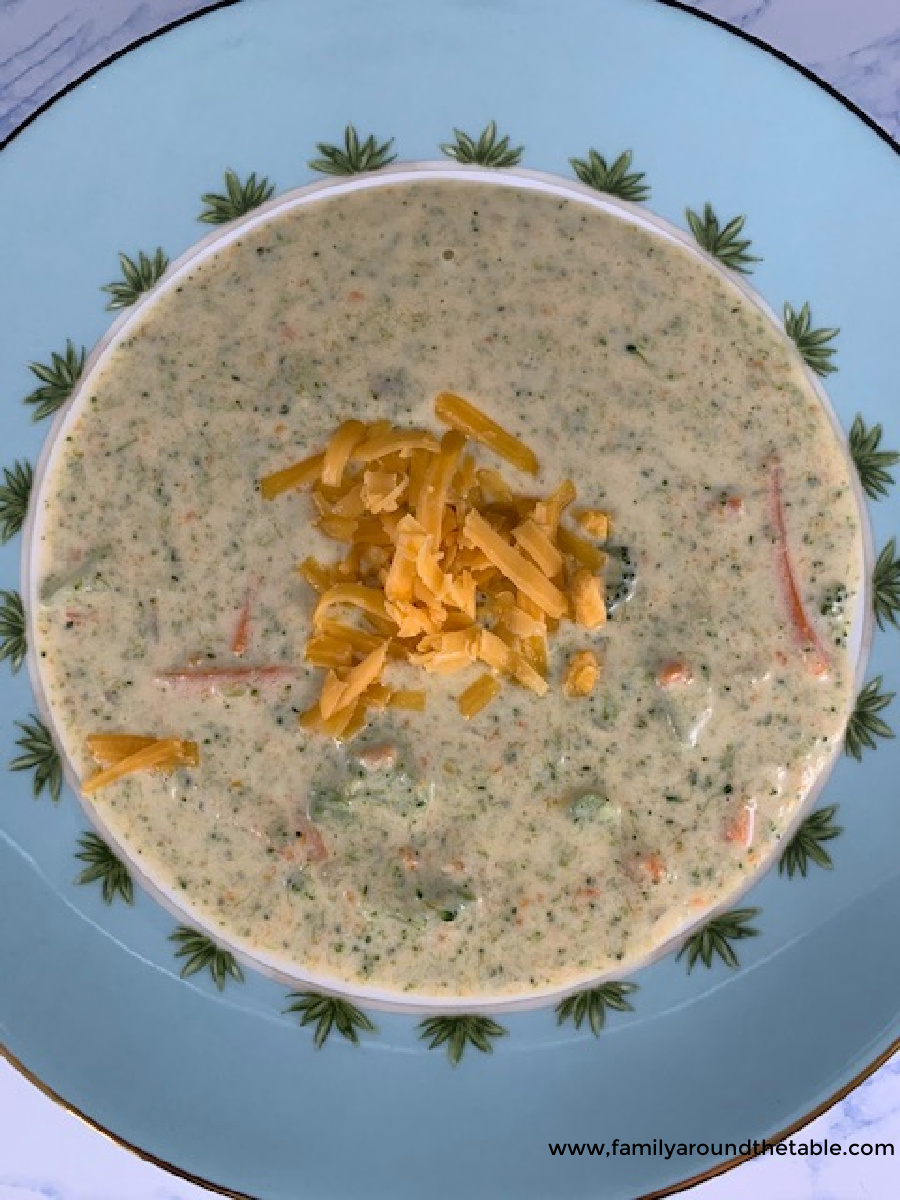 Overhead photo of broccoli cheddar soup garnished with shredded cheese.