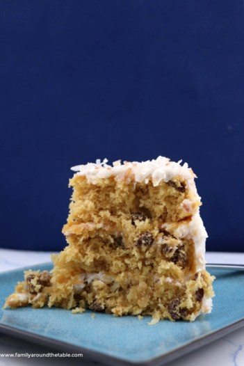 Slice of 3 layer coconut cake on a blue plate.