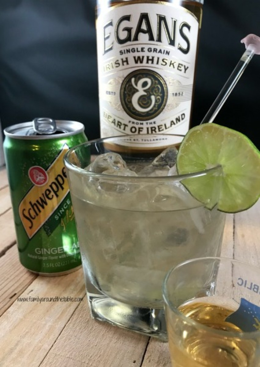 An Irish Buck cocktail with a bottle of Irish whiskey and can of ginger ale.