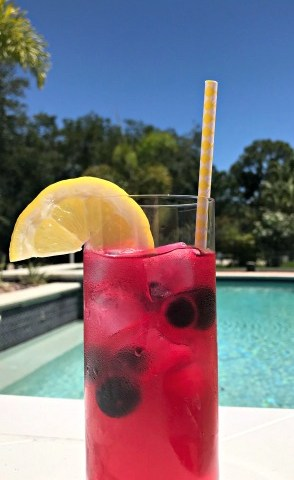 A glass of blueberry lemonade with a lemon slice garnish with a pool in the background.