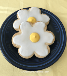 2 daisy shortbread cookies on a blue plate on a yellow cloth.