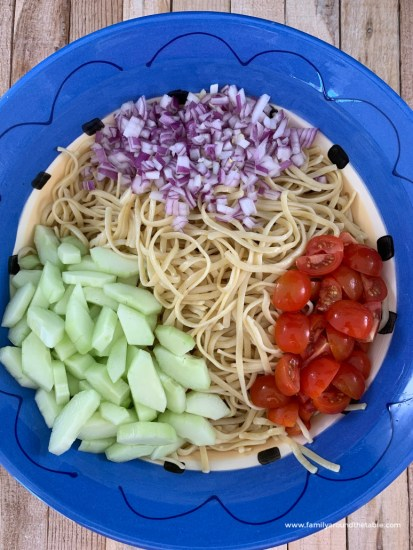 red onion, tomato, cucumber and linguine in a blue bow.