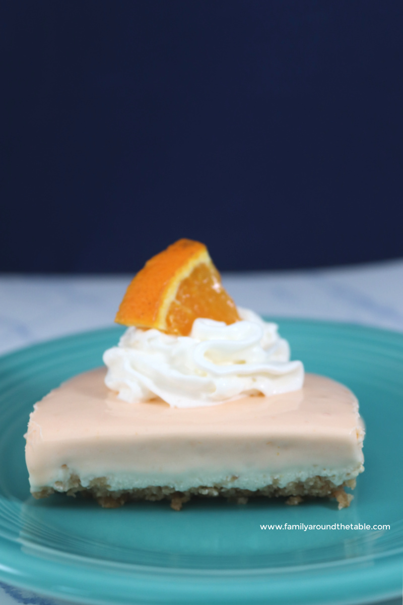A square of no bake orange creamsicle bar on a teal plate.
