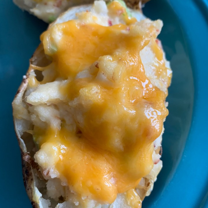 One twice baked potato on a blue plate.