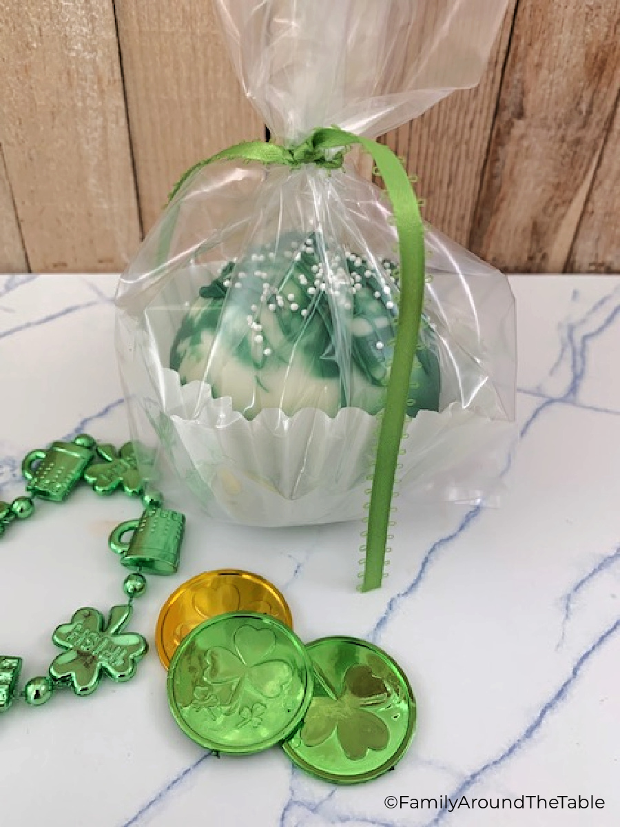 A cocoa bomb in a cupcake liner wrapped in cellophane and tied with green ribbon.
