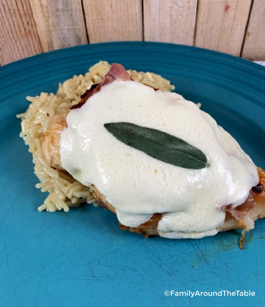 Chicken saltimbocca on a blue plate served with rice.