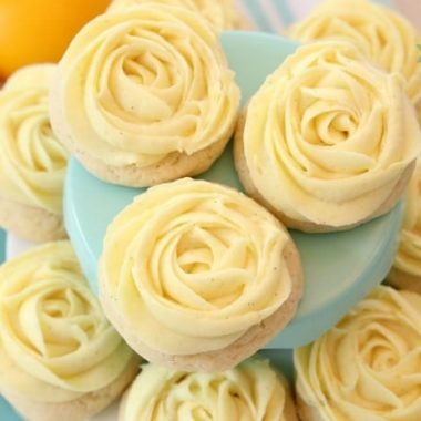 Lemon Sugar Cookies made by adding fresh lemon juice and zest to a simple sugar cookie dough. No rolling out or chilling necessary! Just bake and top with a bright lemon buttercream frosting. Easy Lemon Cookies piped with a super simple rosette so they taste incredible and they're pretty too! My all-time favorite Sugar Cookie recipe!