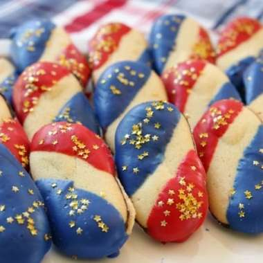 Super Simple 4th of July Cookies made with just 4 ingredients and NO BAKE! Easy red, white and blue cookies made with Milano cookies dipped in red and blue melting chocolate then sprinkled with gold stars. Made in just 15 minutes and they're perfectly patriotic!