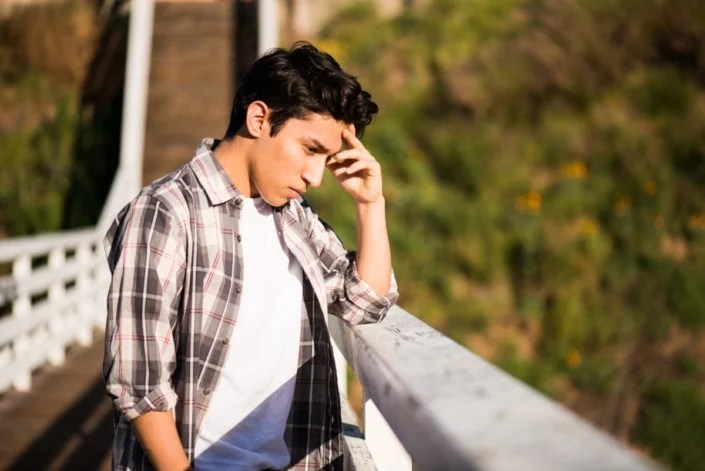 Sad Looking Teenage Boy Standing On A Bridge Thinking About Suicide