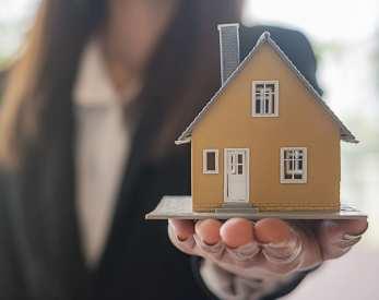 Lady holding house