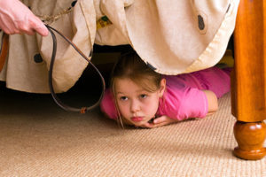 Drawing the Line Between Corporal Punishment and Child Abuse: girl hides under bed for father with belt in hand