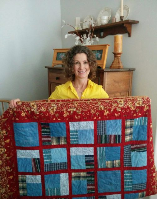 Diana holding her dad's quilt