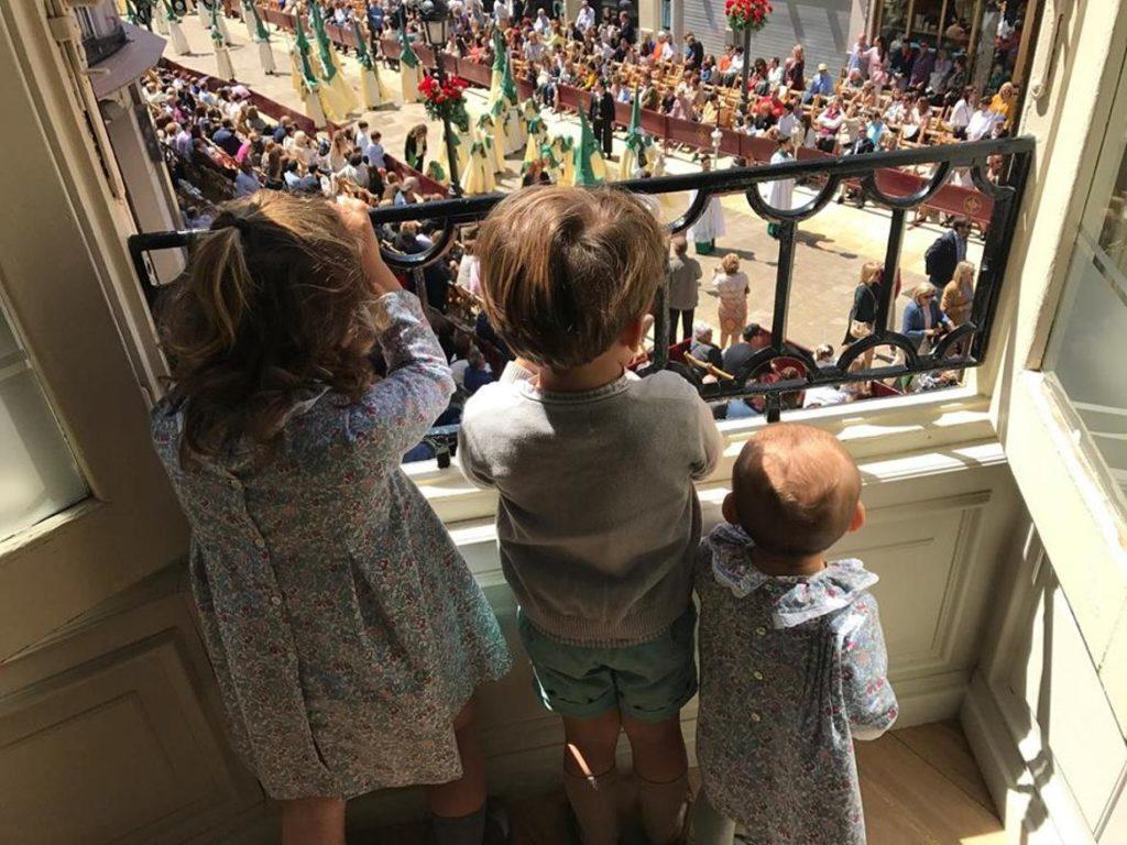 Niños contemplando la Semana Santa de Málaga desde un balcón
