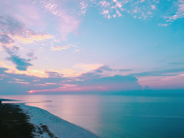 the sky is vivid blue and pink as the sun rises over the Gulf of Mexico