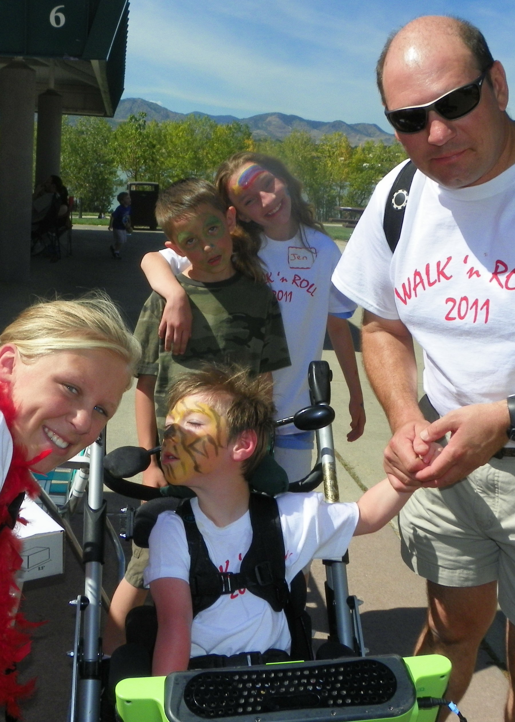 A father holds the hand of a child in a wheelchair as two other children and a youth volunteer, all with their faces painted, look on, at the 2011 Walk 'n' Roll