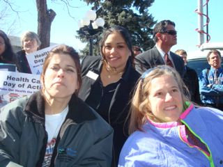 A woman stands behind two other women who are seated in wheelchairs. People behind them hold signs for Health Care Day of Action.