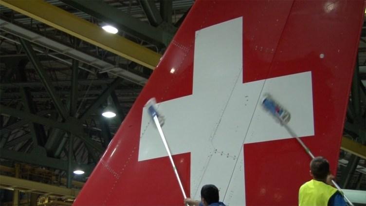 solventi non abrasivi, spugne, bastoni a lunghezza variabile e olio di gomito: si lava il timone di coda di un Swiss International Air Lines Airbus A320