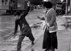 Between Showers - Charlie Chaplin the Little Tramp trying (and failing) to help a pretty girl across a flooding street