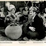 In the department store, Harpo acts as a snake charmer while Groucho and the crowd looks on in The Big Store