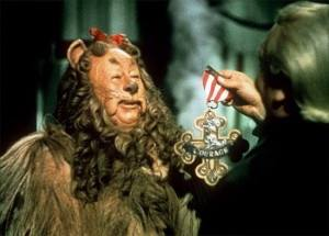 "Bert Lahr, in costume as the Cowardly Lion in the Wizard of Oz, being given his medal for ""Courage"""
