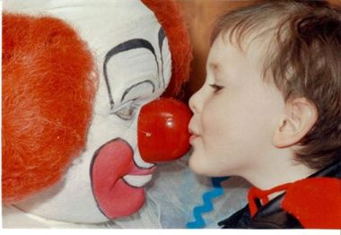 Bozo the clown being kissed on the nose by a young child
