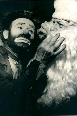 Emmett Kelly clowning with Santa Claus