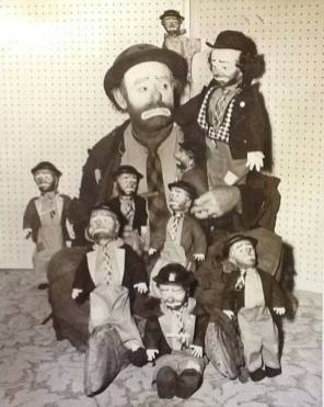 Emmett Kelly surrounded by doll likenesses