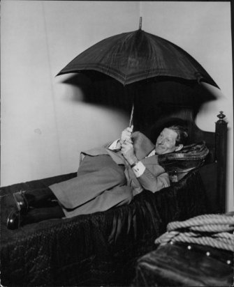 Danny Kaye on a bed with an umbrella