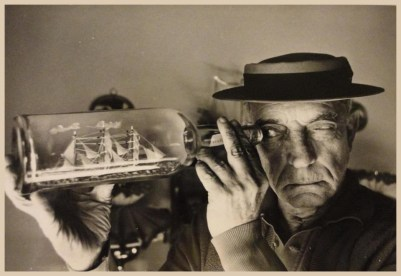 Buster Keaton looking at a ship in a bottle