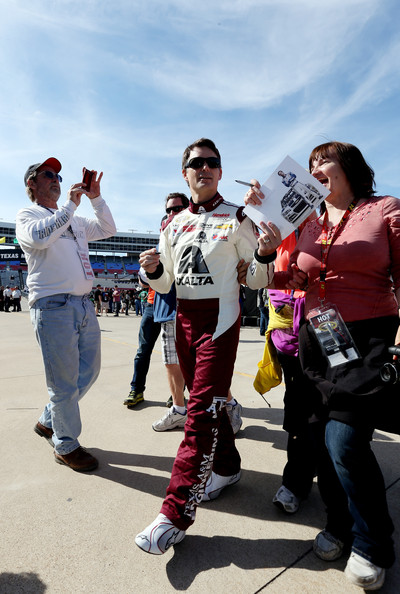 Jeff Gordon, driver of the #24 Axalta/Texas A&M School of Engineering Chevrolet, signs autographs during practice for the NASCAR Sprint Cup Series race at Texas Motor Speedway on April 4, 2014