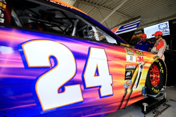 Chase Elliott, driver of the #24 SunEnergy1 Chevrolet, talks with a crew member in the garage area during practice for the NASCAR Sprint Cup Series Hollywood Casino 400 at Kansas Speedway on October 14, 2016 in Kansas City, Kansas. Photo - Chris Trotman/Getty Images