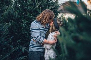 Hippie-Couple-Kissing-Between-Christmas-Trees