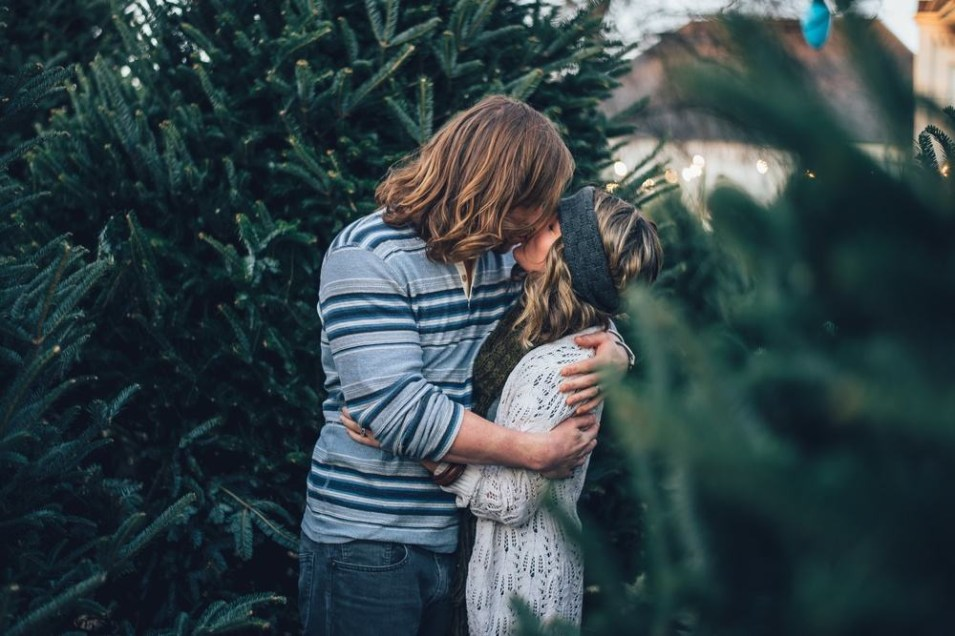 Hippie Couple Kissing Between Christmas Trees