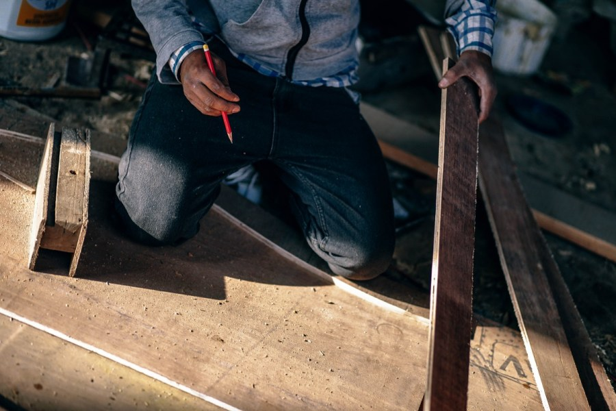 Hands of a skilled craftsman measuring a wooden plank.