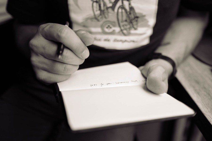 Young-man-writing-down-his-ideas-inside-a-plain-notebook