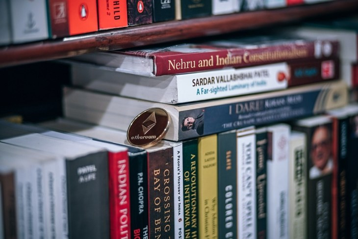 Ethereum-Cryptocurrency-Coin-Laying-on-Top-of-Books-Inside-a-Bookstore-min