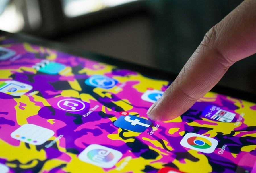 Finger-Opening-Facebook-App-on-an-Ipad-min