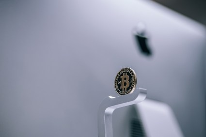 Gold-Bitcoin-Coin-Behind-an-iMac-at-the-Apple-Store-min