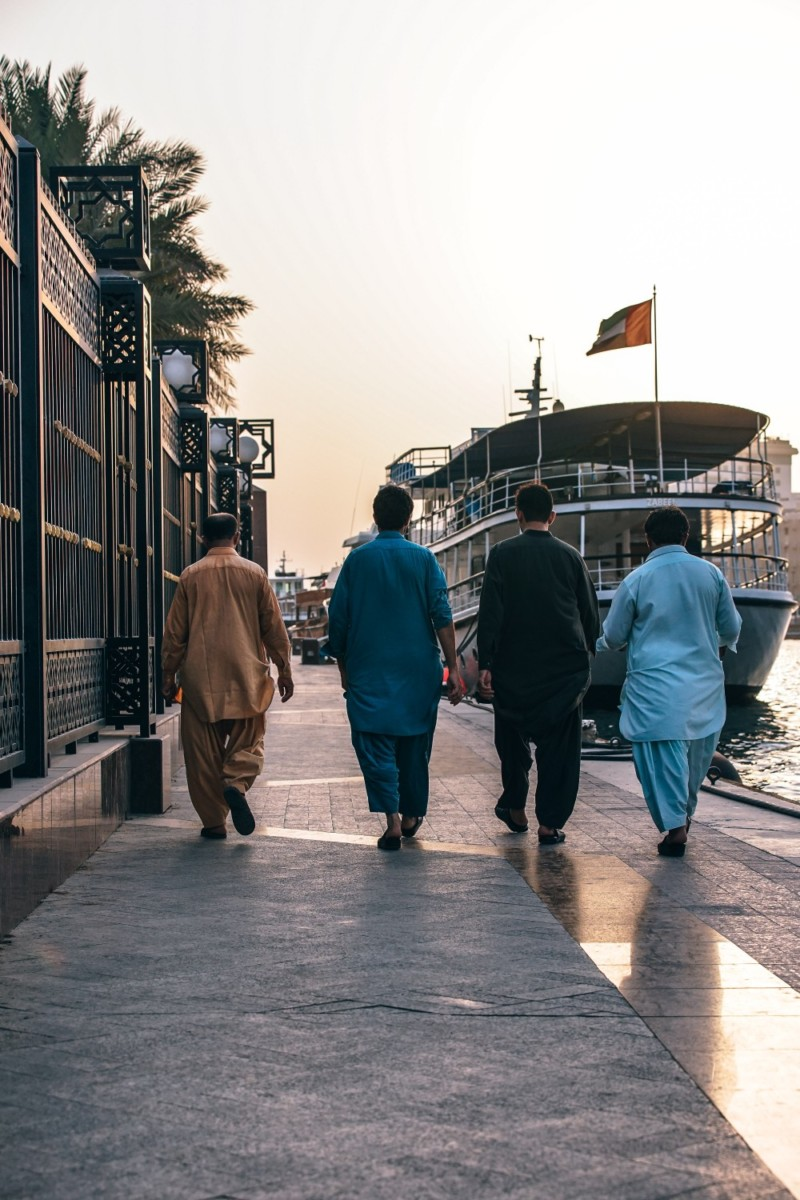Four-Men-Walking-along-the-Dubai-Marina-next-to-the-Canal