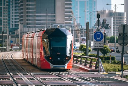 Red-and-Black-Tram-waiting-on-a-Traffic-Light-in-Dubai