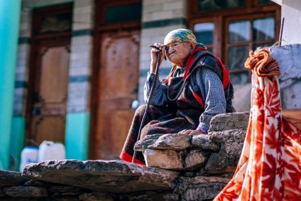 Older-Woman-Sitting-on-Stone-Stairs-in-Manali-and-Thinking