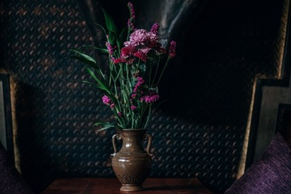 Vase-Full-of-Pink-Flowers-Placed-in-front-of-a-Black-Wall