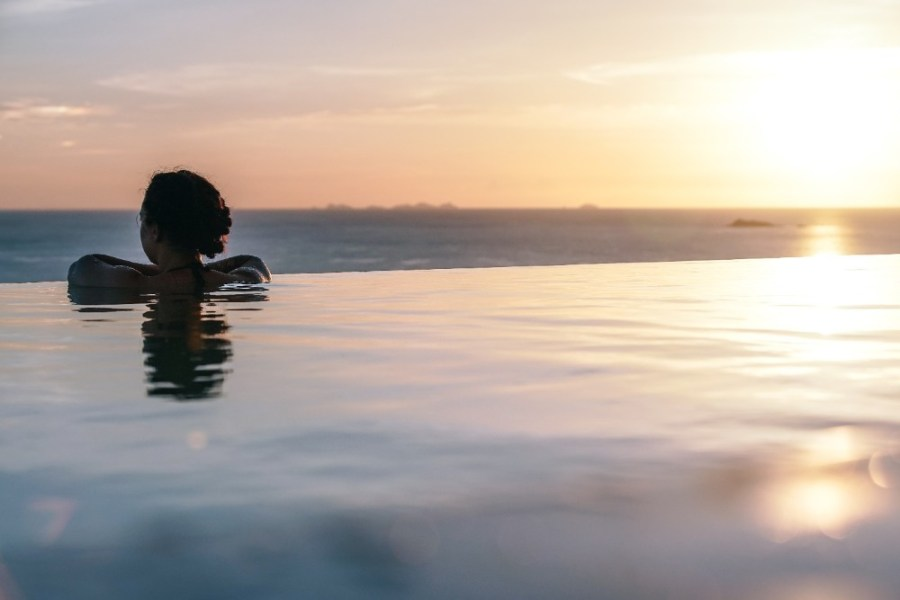 Woman-Overlooking-the-Sea-Coast-from-Infinity-Pool
