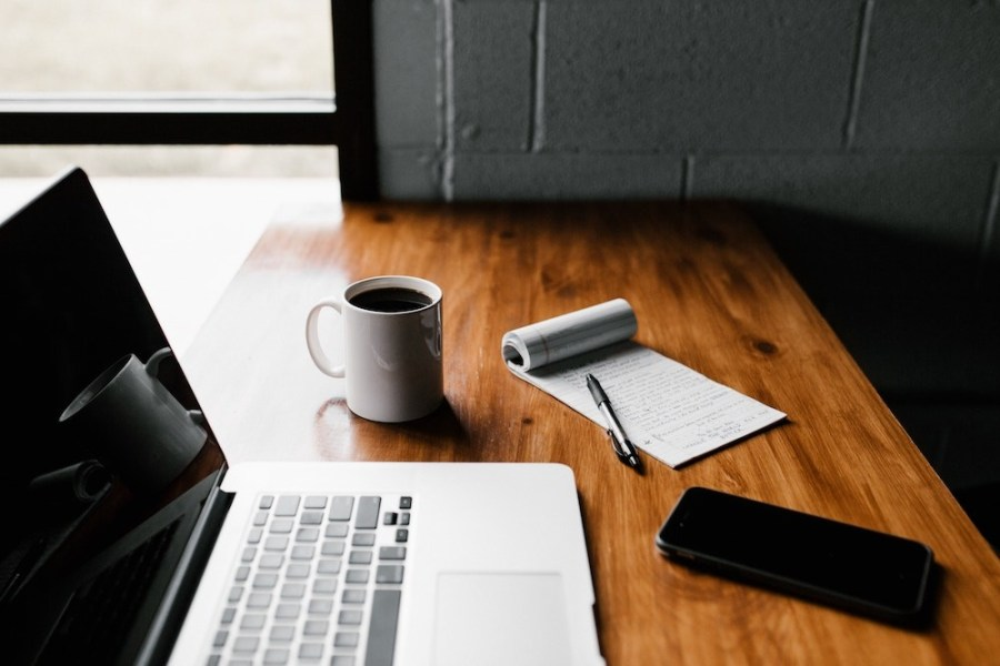 MacBook-Pro-white-ceramic-mugand-black-smartphone-on-table