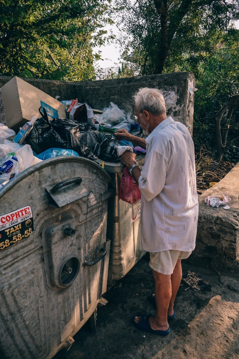 Man-Looking-Through-Trash-Containers