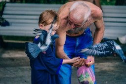 Man-Teaching-a-Young-Kid-how-to-Feed-Birds
