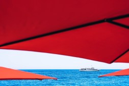 Passenger-Boat-Riding-in-the-Black-Sea-Photographed-Through-Red-Umbrellas