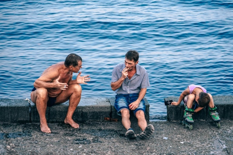 Two-Men-and-a-Kid-Sitting-By-the-Sea-in-Yalta