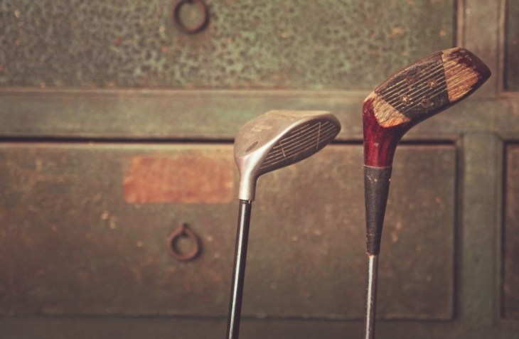Vintage-Golf-Clubs-in-Front-of-a-Wooden-Drawer