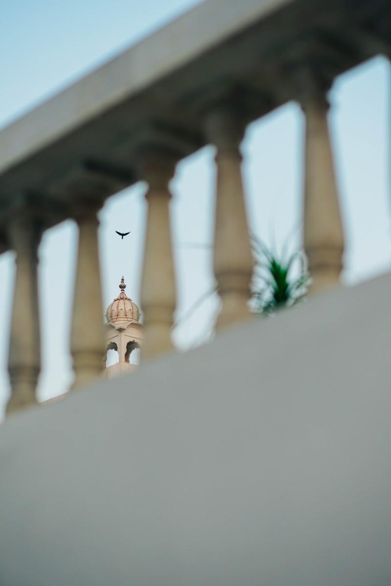Bird-Flying-Over-Gurudwara-Bangla-Sahib-Photographed-Through-a-Stone-Fence